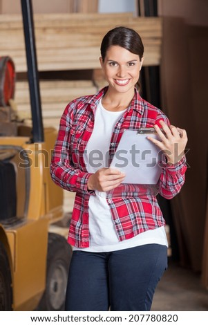 Portrait of confident female supervisor holding clipboard while in workshop - stock photo
