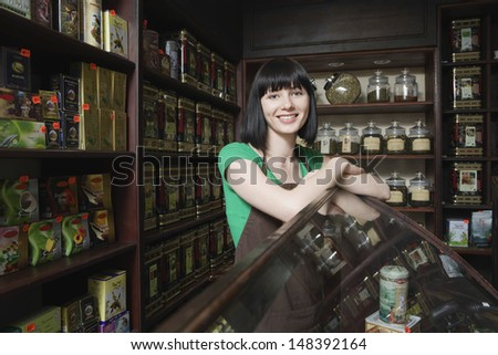 Portrait of confident female tea shop owner leaning on display cabinet - stock photo