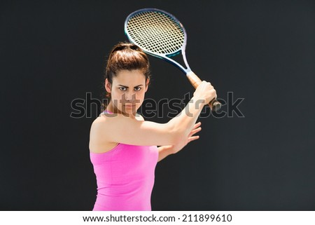 Portrait of confident female tennis player with racquet over black background - stock photo