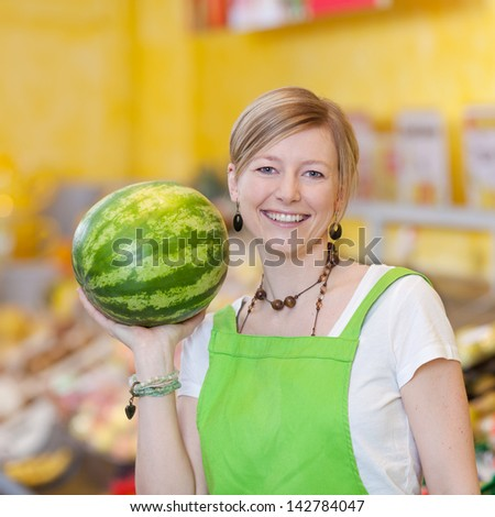 Portrait of confident female worker holding watermelon in grocery store