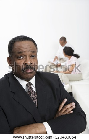 Portrait of confident financial adviser with couple in background - stock photo