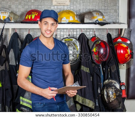 Portrait of confident firefighter holding clipboard at fire station - stock photo