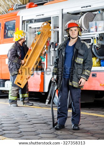 Portrait of confident firefighter holding hose with colleague carrying stretcher by truck at fire station