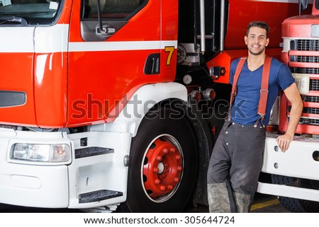 Portrait of confident firefighter leaning on truck at fire station - stock photo