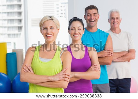 Portrait of confident fit people standing arms crossed at gym - stock photo