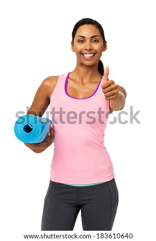 Portrait of confident fit woman gesturing thumbs up while holding exercise mat over white background. Vertical shot. - stock photo