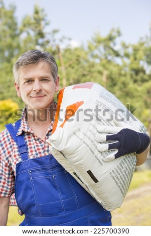 Portrait of confident gardener carrying sack in plant nursery - stock photo