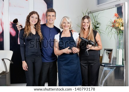 Portrait of confident hair styling team standing together in salon - stock photo