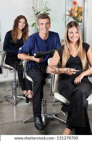 Portrait of confident hairstylists sitting on chairs in salon - stock photo