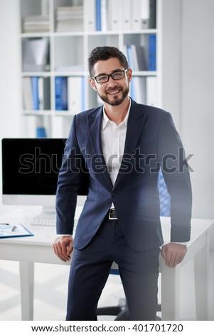 Portrait of confident handsome entrepreneur standing at his desk - stock photo