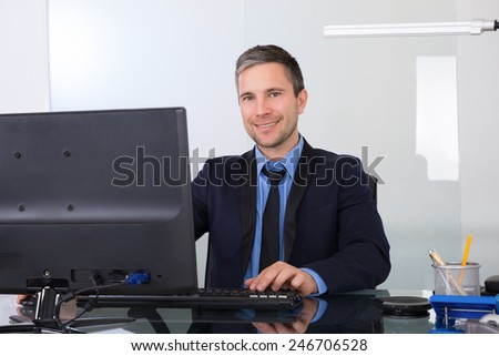 Portrait Of Confident Happy Businessman Using Computer In His Office - stock photo