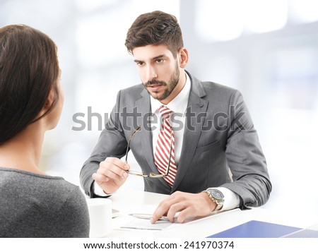 Portrait of confident investment advisor giving advise for busy business woman, while sitting at office.  - stock photo