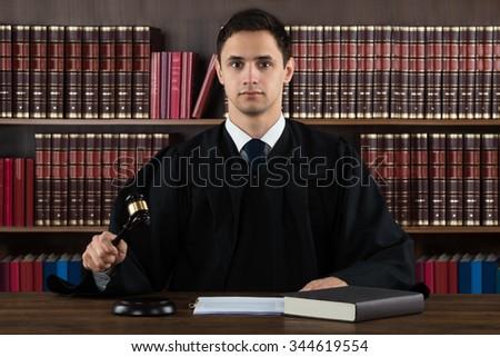 Portrait of confident judge hitting mallet at desk against bookshelf in courtroom - stock photo
