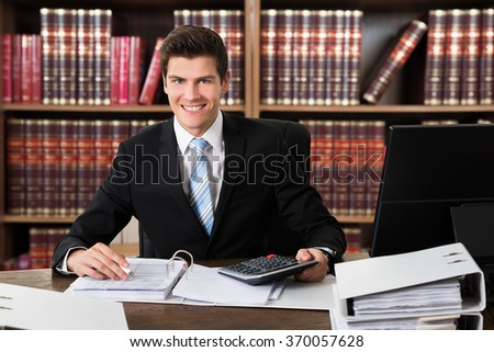 Portrait of confident lawyer using calculator while writing on documents at desk in office - stock photo