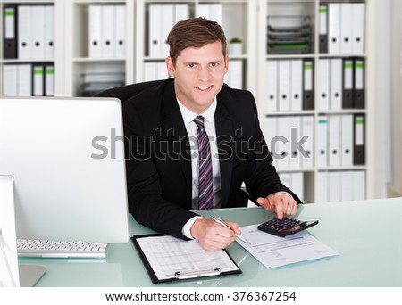 Portrait of confident male accountant using calculator at desk in office