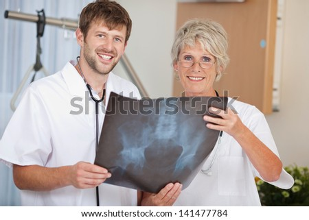 Portrait of confident male and female doctors holding Xray report in hospital - stock photo
