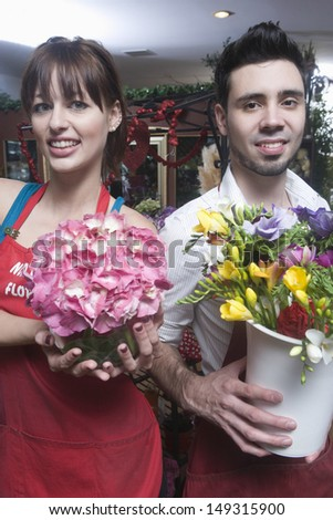 Portrait of confident male and female florists holding flower vases in shop - stock photo