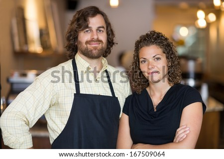 Portrait of confident male and female owners standing together in cafe - stock photo