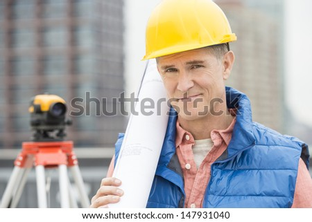 Portrait of confident male architect holding rolled up blueprint at construction site