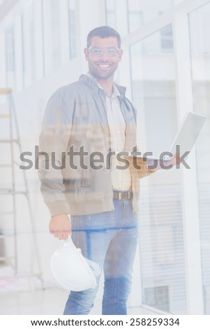 Portrait of confident male architect with hardhat and laptop in office - stock photo