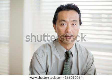 Portrait of confident male cancer specialist in shirt and tie at clinic - stock photo