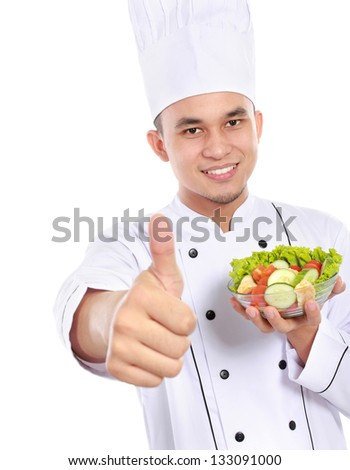 Portrait of confident male chef eating healthy food showing thumb up - stock photo