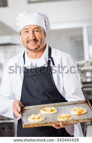 Portrait of confident male chef holding small pizzas on baking sheet in commercial kitchen - stock photo