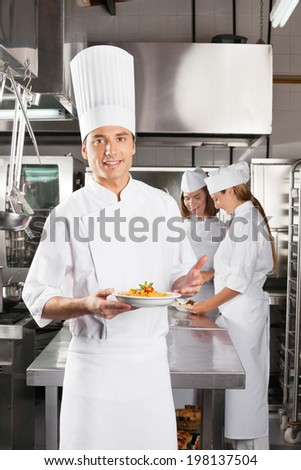 Portrait of confident male chef presenting dish with colleagues standing in background at commercial kitchen - stock photo