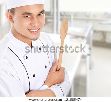 Portrait of confident male chef smiling in the kitchen - stock photo