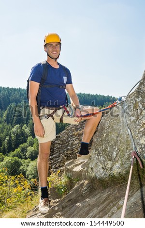 Portrait of confident male climber with climbing equipment standing on rock - stock photo