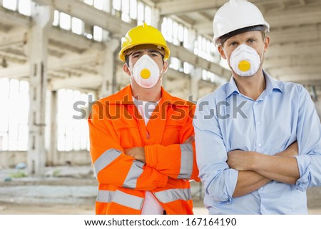 Portrait of confident male construction workers in protective workwear at site - stock photo