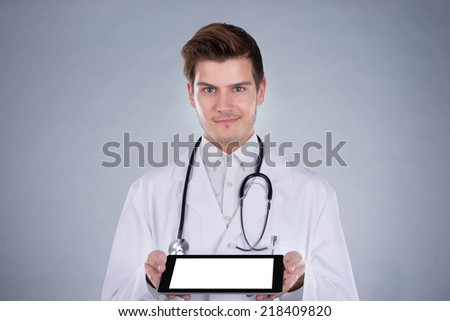 Portrait of confident male doctor holding digital tablet over gray background - stock photo