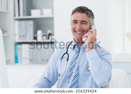 Portrait of confident male doctor using telephone in clinic - stock photo