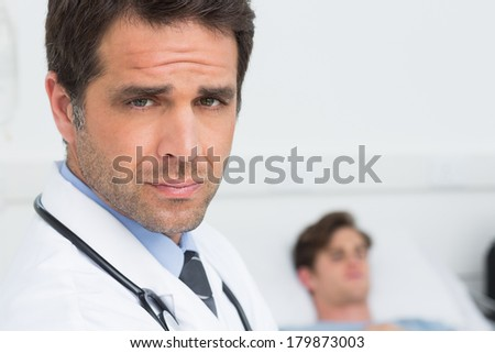 Portrait of confident male doctor with male patient in background at hospital ward