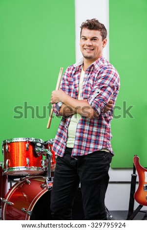 Portrait of confident male drummer standing arms crossed in recording studio - stock photo