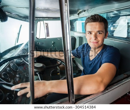 Portrait of confident male firefighter driving firetruck - stock photo