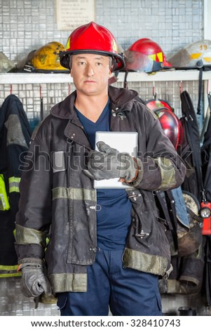 Portrait of confident male firefighter in uniform holding digital tablet at fire station