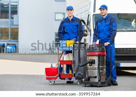 Portrait of confident male janitors with cleaning equipment standing on street - stock photo