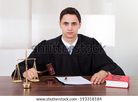 Portrait of confident male judge sitting at table in courtroom - stock photo