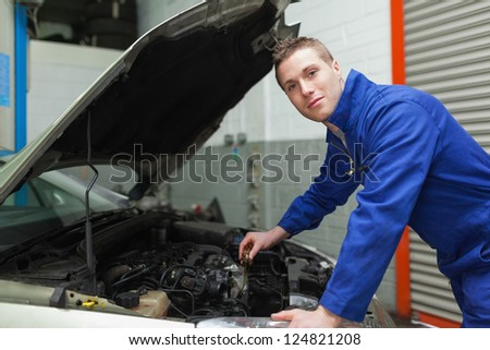 Portrait of confident male mechanic checking car engine oil - stock photo