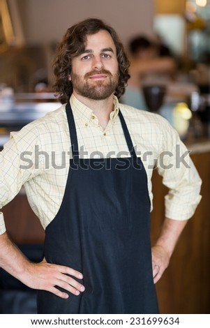 Portrait of confident male owner with hands on hips standing in cafeteria - stock photo