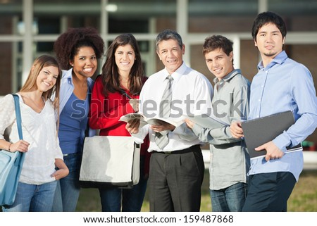 Portrait of confident male professor and students standing on university campus - stock photo