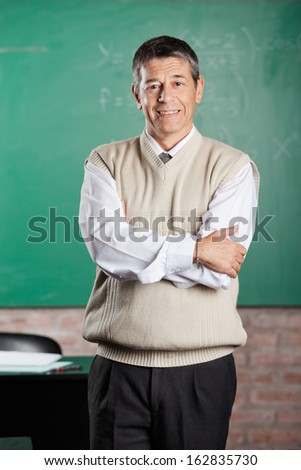 Portrait of confident male professor standing arms crossed in classroom - stock photo