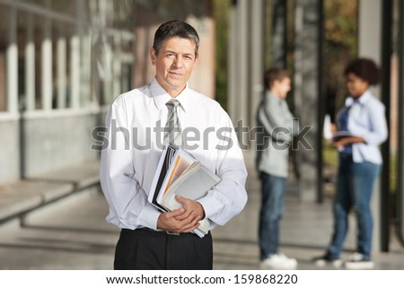 Portrait of confident male professor with books standing on college campus - stock photo