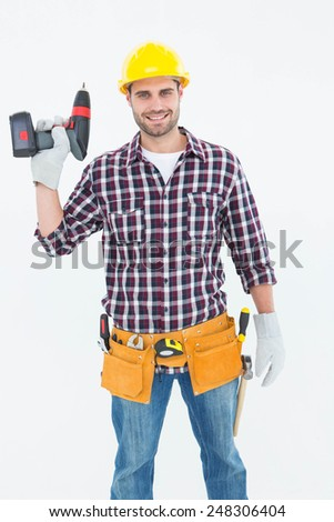 Portrait of confident male repairman holding drill machine on white background - stock photo