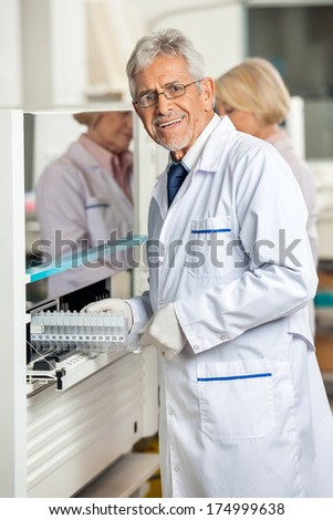Portrait of confident male researcher loading samples in analyzer at laboratory - stock photo
