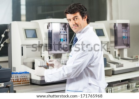 Portrait of confident male scientist using urine analyzer to test samples in medical lab - stock photo