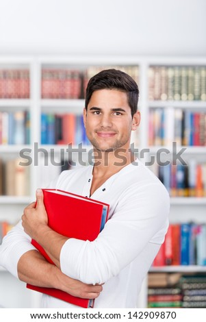 Portrait of confident male student holding binder in library - stock photo