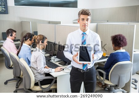 Portrait of confident manager holding tablet computer while customer service executives working in background at call center - stock photo