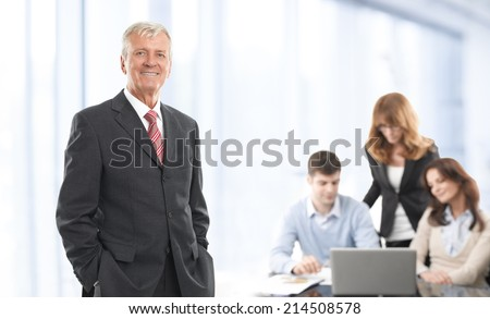 Portrait of confident manager standing at office with colleagues at background. - stock photo